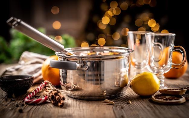 축제 조명 앞 나무 테이블에 mulled 와인 준비를 위한 강철 냄비와 재료