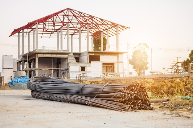 Steel rebar for reinforcement concrete at construction site with house under construction background