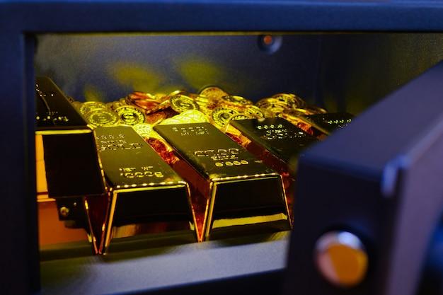 Steel safes box full of coins stack and gold bar on the wooden table