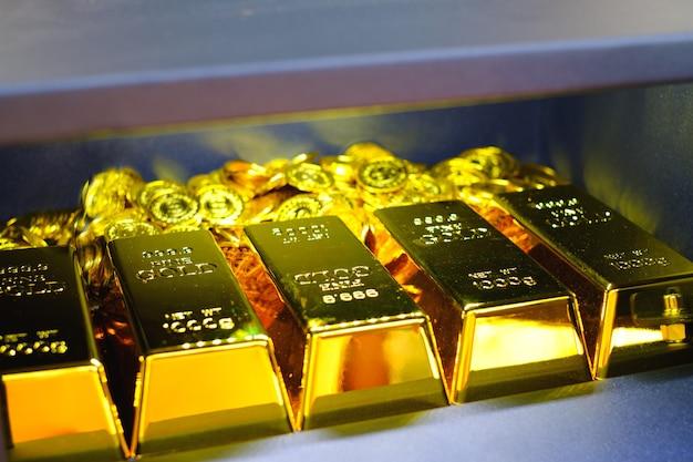 金の棒のスタックとコインでいっぱいの鋼の金庫ボックス