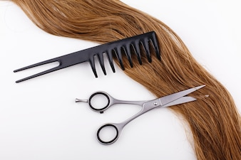 Steel scissors lie on the wave of silk brown hair with a black comb