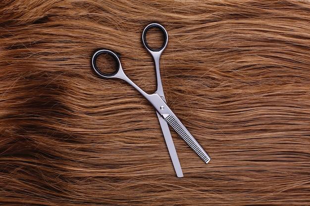 Steel scissors lie on the wave of silk brown hair