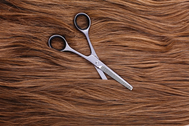 Steel scissors lie on the wave of silk brown hair