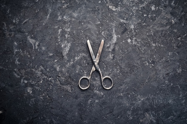 Steel scissors for needlework on a concrete surface. top view.