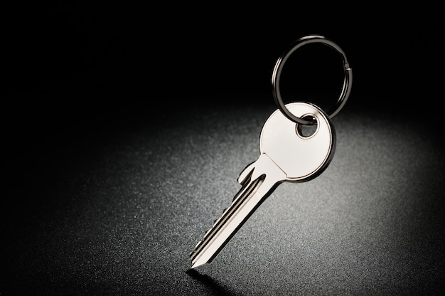 Steel shiny key with ring on a black textured background
