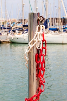 Steel shiny pillar with metal chain on the background of sailing yachts