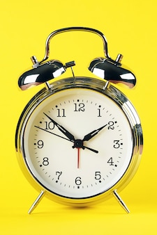 Steel silver alarm clock in retro style on a bright yellow background. close up.