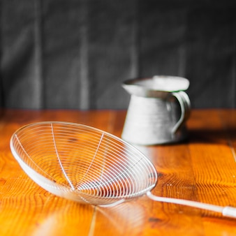 Steel skimmer in front of old jug on wooden table