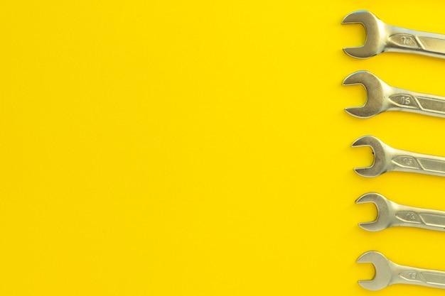 Ключи стальные разных размеров и диаметров на желтом фоне. набор ключей хром-ванадиевых. металлический инструмент для ремонта автомобилей, сантехники, станков. плоская планировка, прекрасный вид. скопируйте пространство.