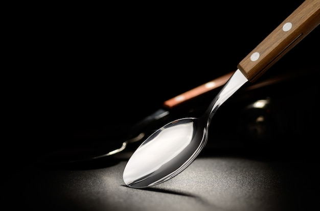 Steel spoon on the black grained surface