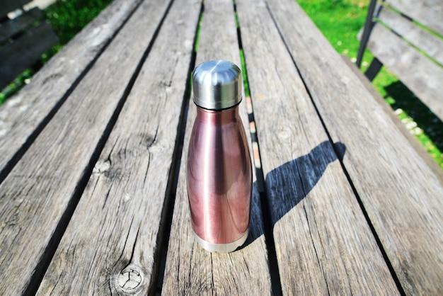 木製のテーブルにモックアップが付いたスチール製のステンレス製エコサーモウォーターボトルプラスチックを使用しないゼロウェイストコピースペースゼロ廃棄物プラスチックの持続可能性