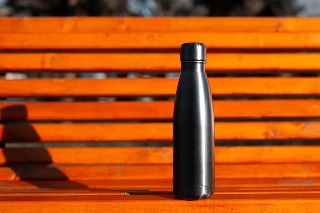 Steel stainless thermo water bottle of black on background of orange wooden bench with copy space. reusable bottles zero waste eco concept plastic free.