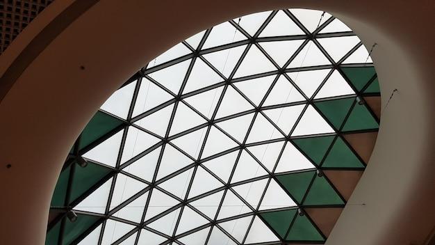 Стальная конструкция потолка крыши из металла и стекла с фоном голубого неба. современная элегантная торговая архитектура в торговом центре.