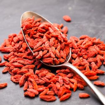어두운 배경에 빨간색 말린 구기 열매의 강철 스푼