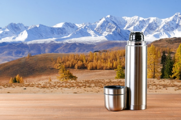 Steel thermos on wooden table in mountains background.