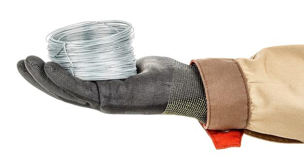 鋼線コイルは、黒の保護手袋と白の茶色のユニフォームで労働者の手のひらにあります