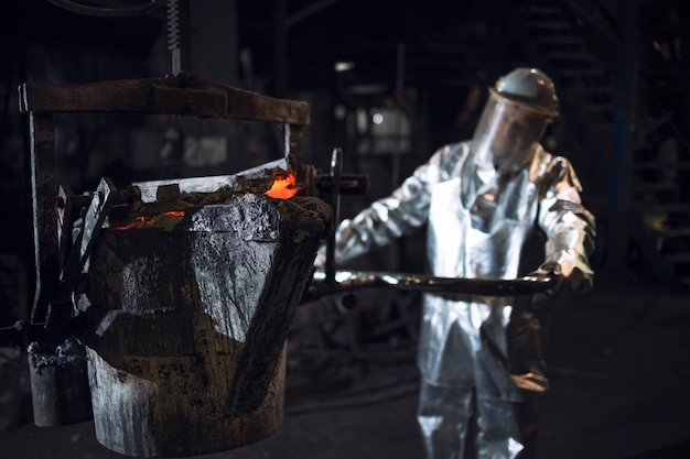 Steel worker in protective fire suit pushing bucket with molten liquid iron in foundry.