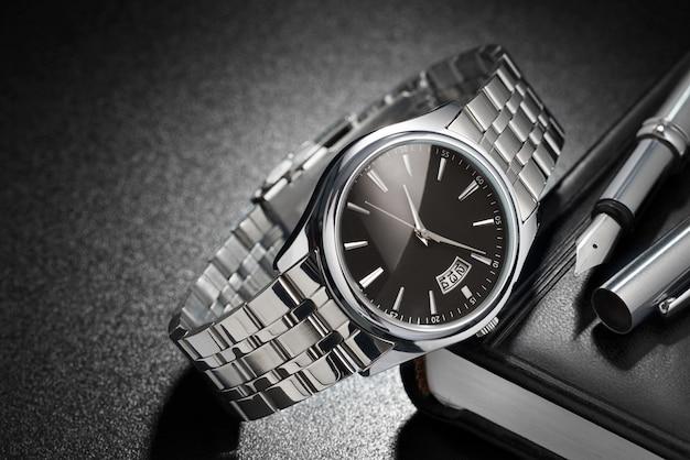 검은 배경에 만년필과 일기가 있는 강철 손목시계