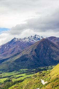 Крутые берега по берегу озера вакатипу снежные шапки гор южный остров новая зеландия