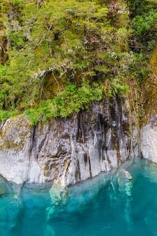 Крутые скалы над голубой водой южный остров новая зеландия