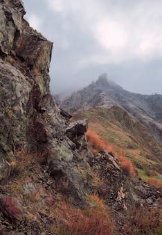 Крутые острые живописные скалы, покрытые желтой травой и мхом в утреннем белом тумане.