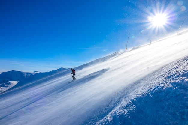 Steep ski slope and bright sun. snowstorm on the surface. skier rides down
