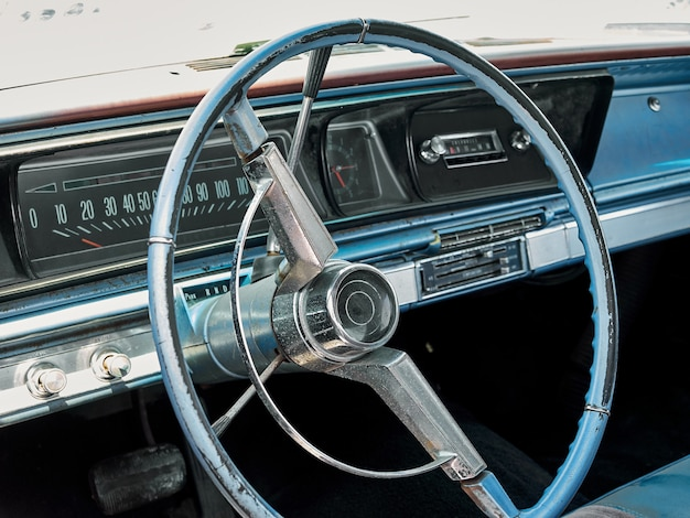 ステアリングホイールと古いレトロなアメリカ車のインテリアのダッシュボードパネル