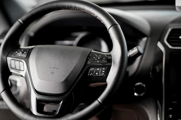 Руль крупным планом внутри нового автомобиля, подушка безопасности, круиз-контроль, выключатель стеклоочистителей и современная приборная панель