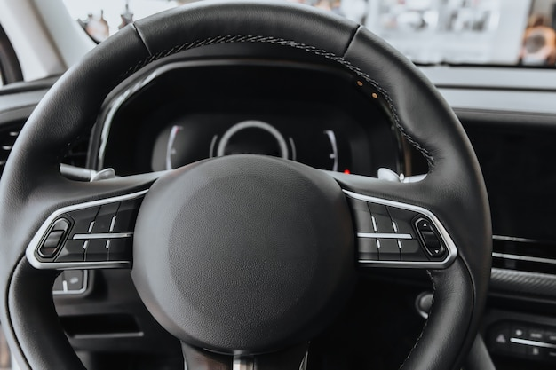 Steering wheel and dashboard of the car in black.