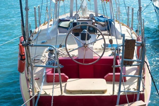 Рулевое колесо на яхте с синим фоном морской воды