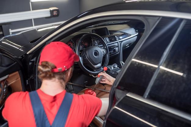 스티어링 휠, 서비스. 자동차 수리점에서 자동차의 스티어링 휠을 수리하는 빨간 모자에있는 남자