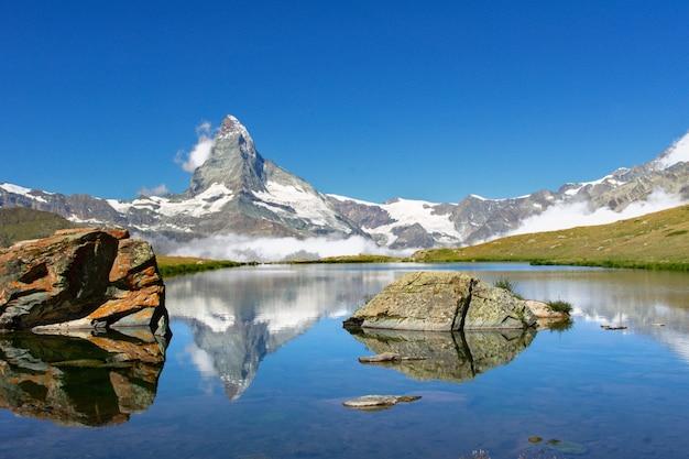 Красивый швейцарский пейзаж альп с отражением в воде, горным видом озера stellisee и горы маттерхорн лета, церматт, швейцария