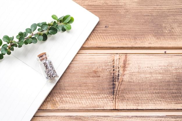 Stem and lavender flower bottle on notebook over the wooden backdrop