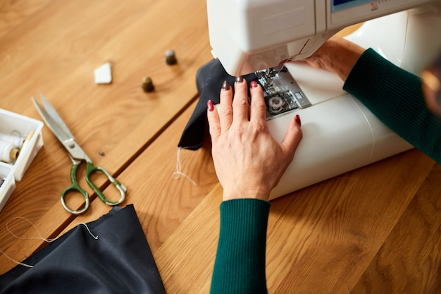 ステップバイステップで、50歳の老婆がミシンで服を縫い、アトリエ、繊維産業、趣味、ワークスペースで縫製を行う成熟した仕立て屋。