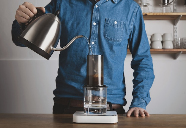 Step by step aero press coffee preparation barista in blue jeans shirt pours hot boiled water from teapot to aeropress professional coffee brewing cafe shop