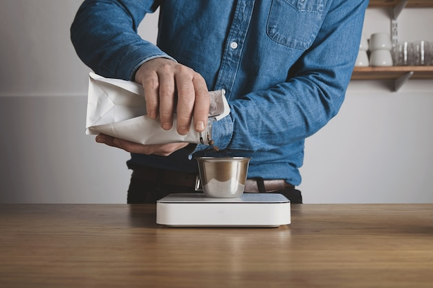 Step by step aero press coffee preparation barista in blue jeans shirt pours roasted beans from bag to steel cup on white weights professional coffee brewing cafe shop