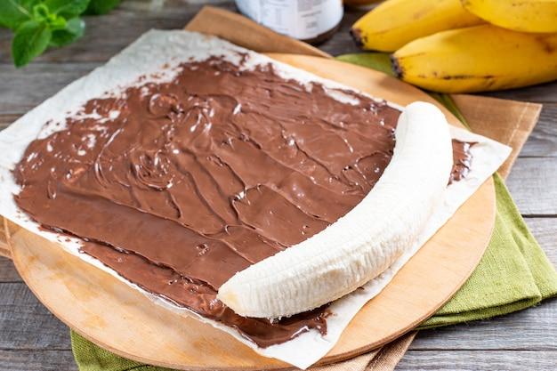 木製のテーブルの上でバナナのスライスを使っておいしいロールを段階的に調理します。バナナロールとチョコレートデザート