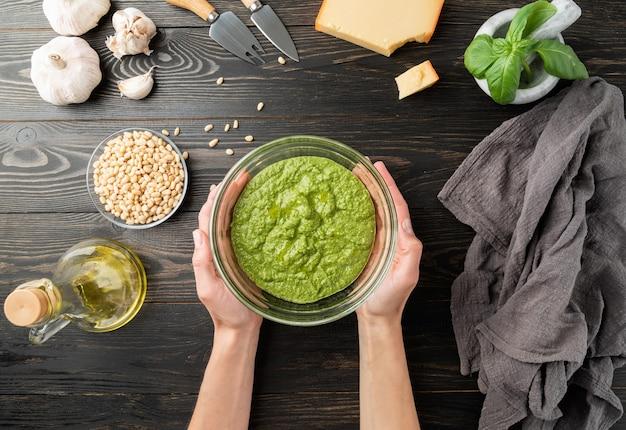이탈리아 페스토 소스를 단계별로 요리합니다. 8단계 - 모든 재료를 섞는다. 페스토 소스가 준비되었습니다. 신선한 녹색 바질, 파마산 치즈, 견과류, 올리브 오일, 마늘 위쪽 전망은 검은색 나무 테이블에 있습니다.