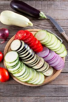 단계별로 라따뚜이 요리. 나무 테이블에 라따뚜이 캐서롤입니다. 프로방스 야채 요리. 다이어트, 완전채식. 라따뚜이 캐서롤.
