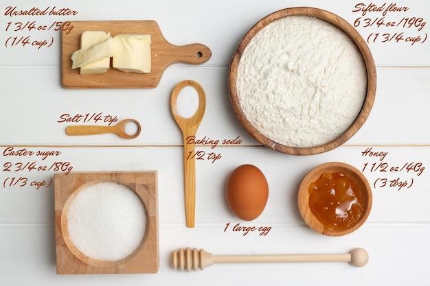 ステップバイステップのハート型のケーキレシピの説明。ベーカリーの材料。バター粉砂糖卵蜂蜜ソーダ塩。フラットレイ。
