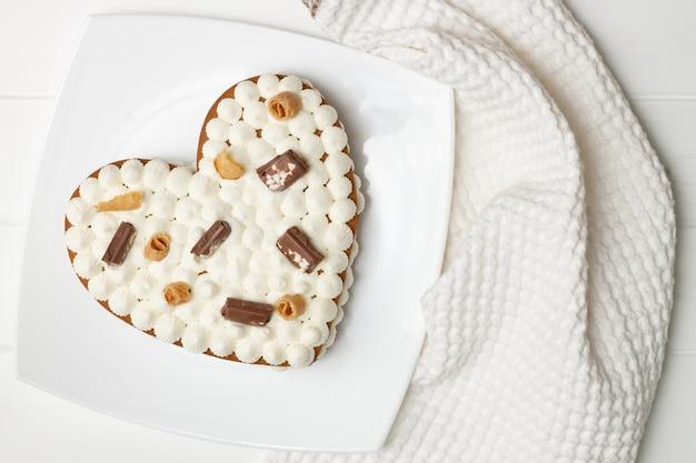 Пошаговая инструкция рецепта торта в форме сердца. украсить торт шоколадной стружкой, вафлями, печеньем. плоская планировка.