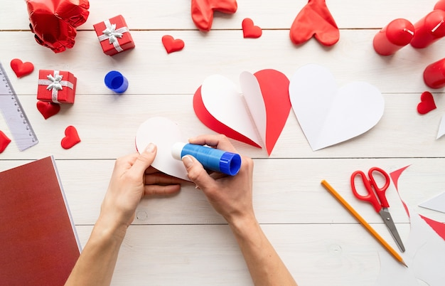 Step by step instruction making paper heart shape hot air balloon. step 5 - glue white sides of hearts to each other so they form a dimensional heart Premium Photo