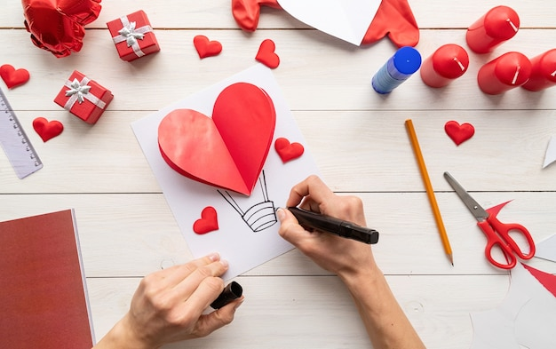 Step by step instruction making paper heart shape hot air balloon. step 7 - use a marker or pen to draw a basket for your hot air balloon