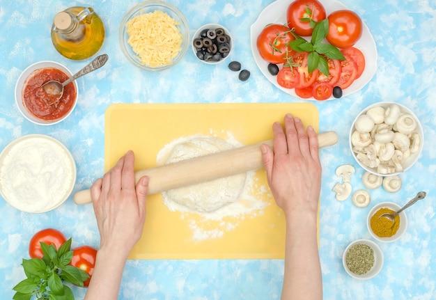 自家製ベジタリアンピザのステップバイステップの準備、ステップ2-生地を広げます