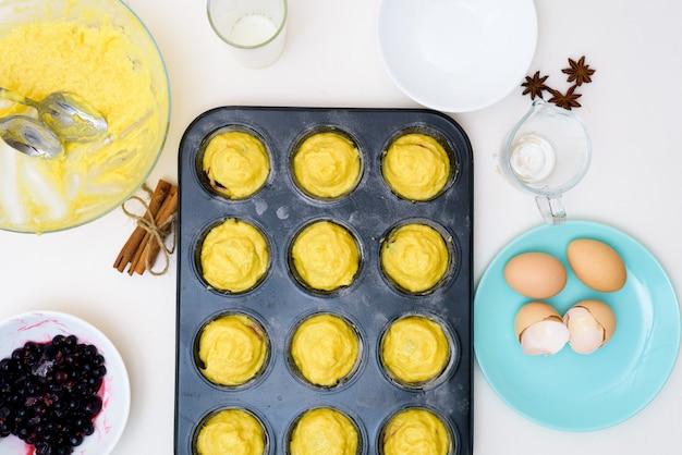 검은 건포도와 머핀에 대한 단계별 제조법. 반죽을 준비하고 밀가루, 버터, 설탕, 계란, 바닐라, 건포도의 성분을 혼합합니다. 위에서 본 모습. 건포도 충전 컵 케이크
