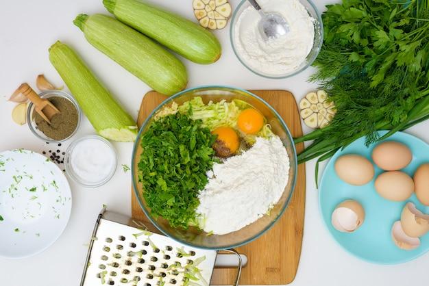 明るい背景でズッキーニとグリーンのパンケーキを調理するための段階的なレシピ。卵、小麦粉、ニンニク、コショウを加えます。上からの眺め