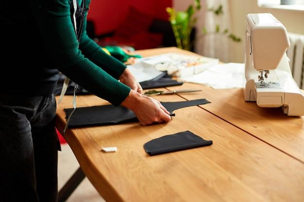 段階的に、女性のドレスメーカーの女性がテーブルの上で縫製パターンを測定し、アトリエ、繊維産業、趣味、仕事場で働く成熟した仕立て屋。製作工程 diy、裁縫師の仕事場。