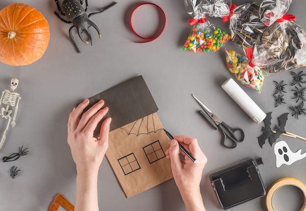 Step-by-step wrapping of a gift for halloween, draw the transverse lines of the web with a felt-tip pen