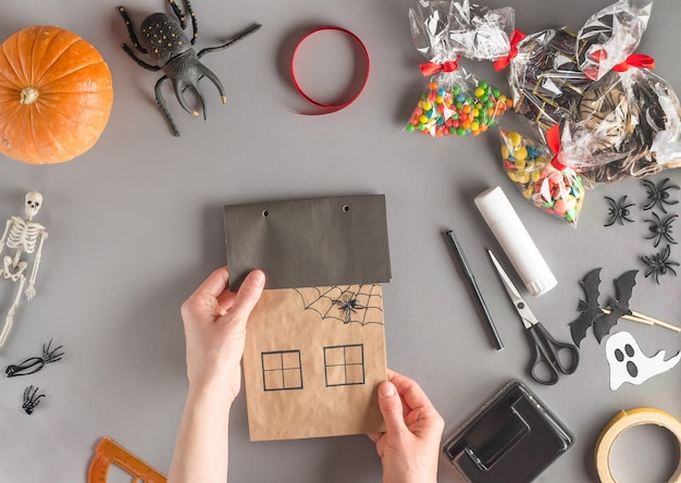 Step-by-step wrapping of a gift for halloween, flat lay, get holes for the tape on the roof of the house