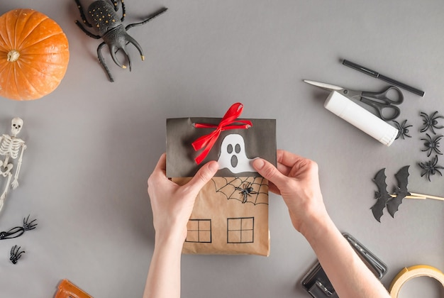 Step-by-step wrapping of a gift for halloween, flat lay. glue the paper ghost